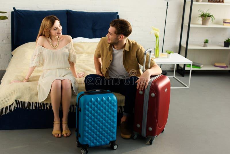 lyckliga par med resväskor som är klara för semestern som sitter på säng arkivfoton