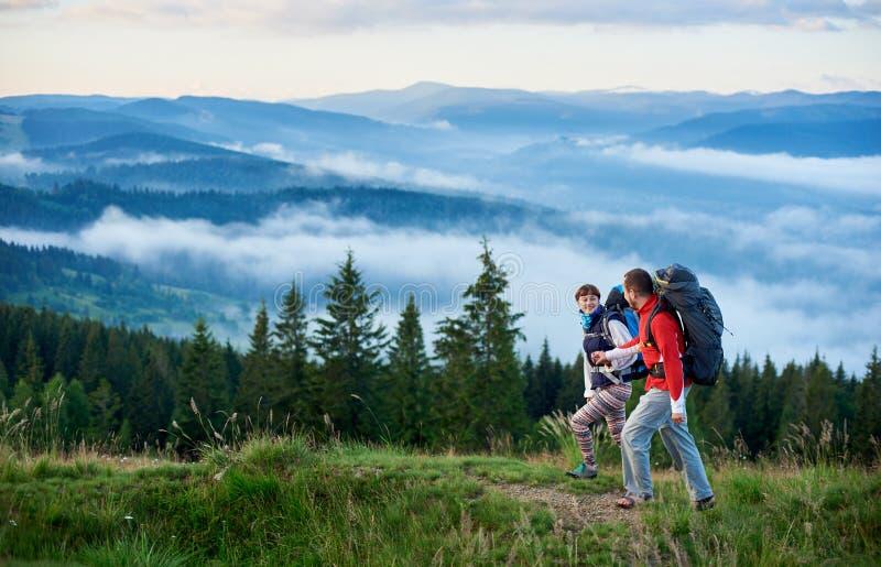 Lyckliga par med ryggsäckar i berg för att gå mot härligt landskap av berg arkivbild