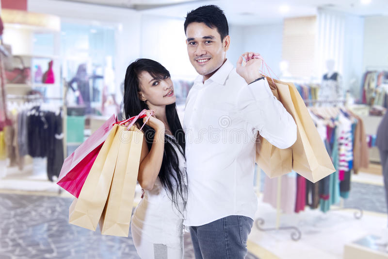 Lyckliga par med shoppingpåsar royaltyfri fotografi