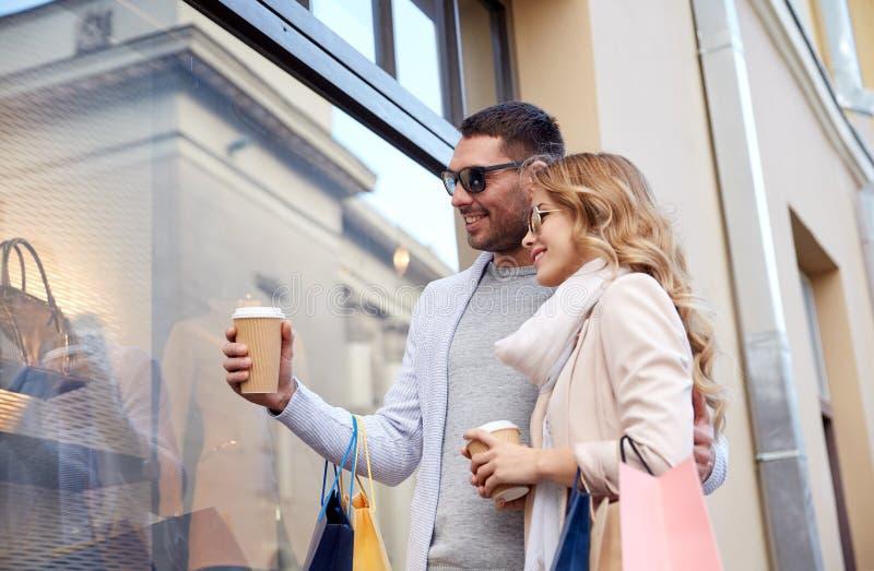 Lyckliga par med shoppingpåsar och kaffe i stad arkivfoton