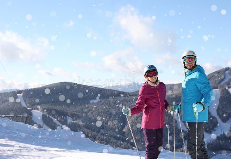 Lyckliga par med skidar semestern för utrustningutgiftervintern i berg arkivbild