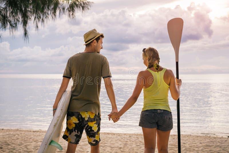 Lyckliga par med skovelbrädet på stranden på solnedgången arkivfoton