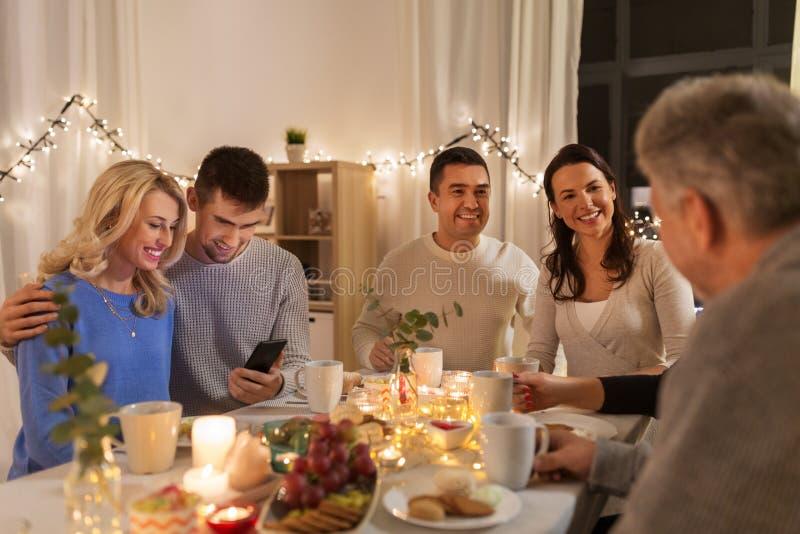 Lyckliga par med smartphonen p? familjtebjudningen royaltyfri fotografi