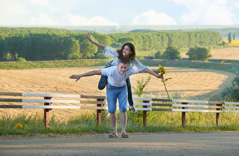 Lyckliga par med solrosor som har roligt och utomhus promenerar landsvägen, flickaridning på hans baksida och flugan - romantiskt royaltyfria bilder