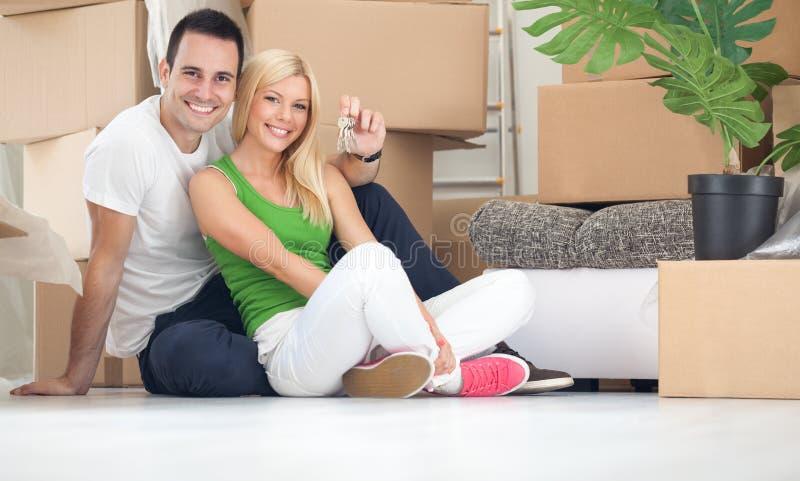 Lyckliga par med tangent av det nya hemmet arkivfoto