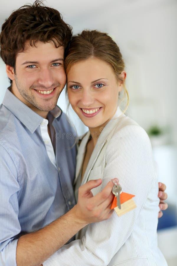 Lyckliga par med tangenter av den nya lägenheten arkivfoto