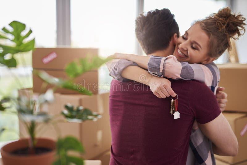 Lyckliga par med tangenter av den nya lägenheten royaltyfri foto