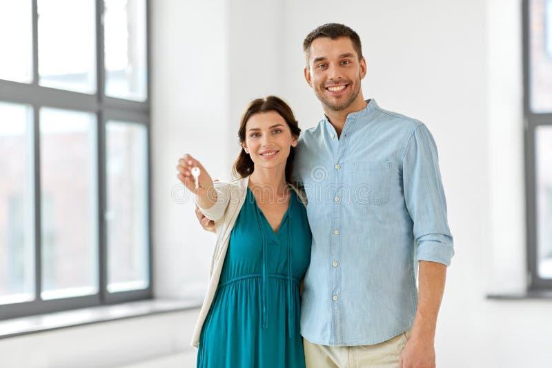 Lyckliga par med tangenter av det nya hemmet arkivfoton