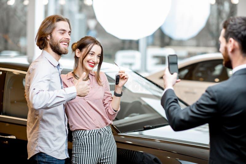 Lyckliga par nära den nya bilen i visningslokalen arkivbilder