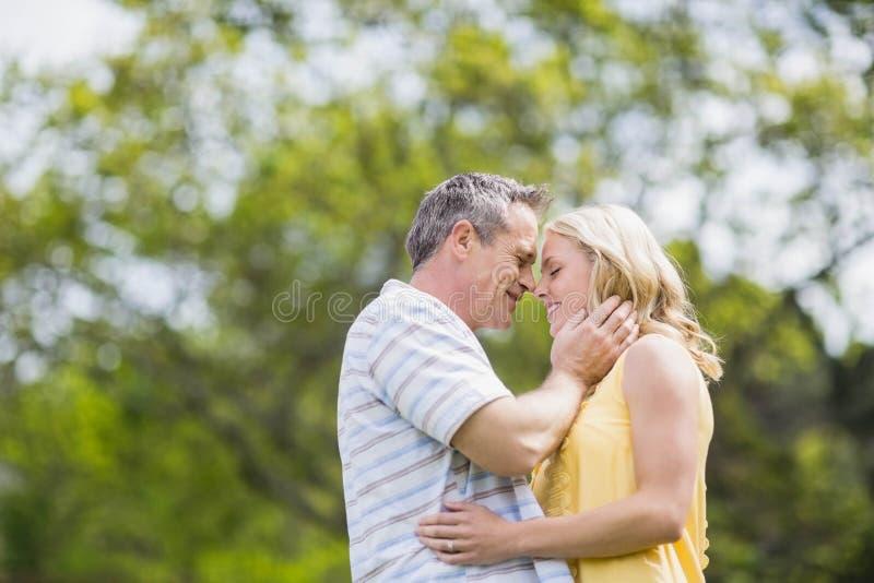 Lyckliga par omkring som ska kyssas arkivfoto