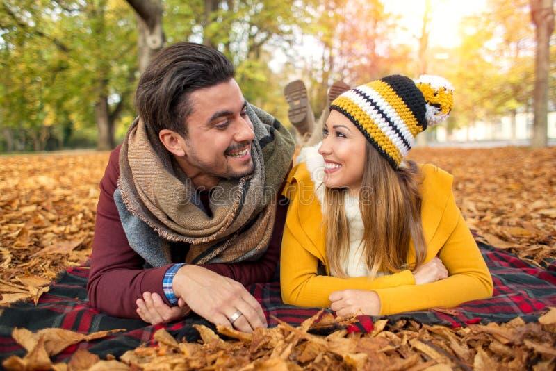 Lyckliga par på en parkera i höst arkivfoto