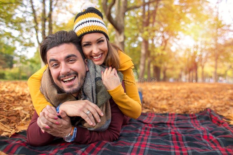Lyckliga par på en parkera i höst royaltyfri fotografi