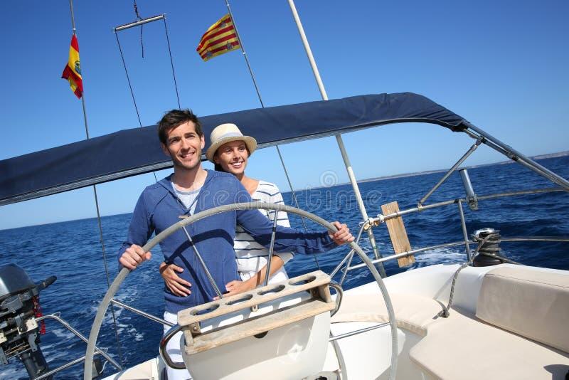 Lyckliga par på en segelbåt royaltyfria bilder