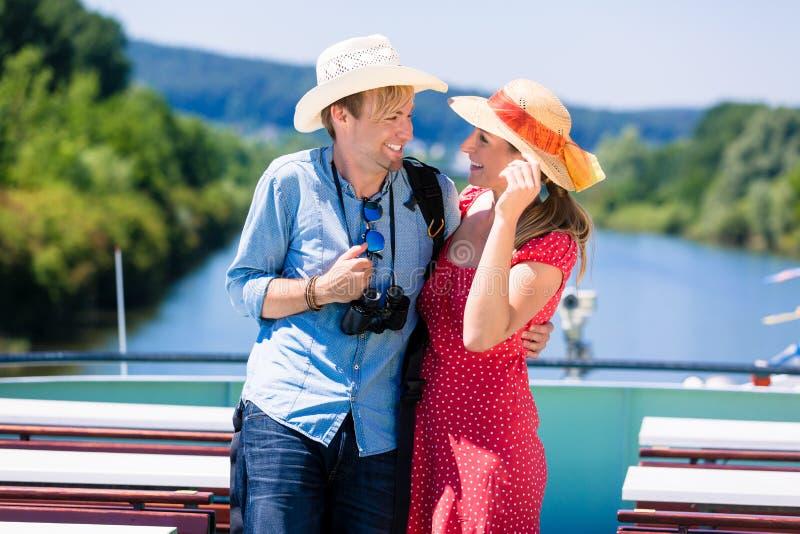 Lyckliga par på floden kryssar omkring bärande solhattar royaltyfria foton