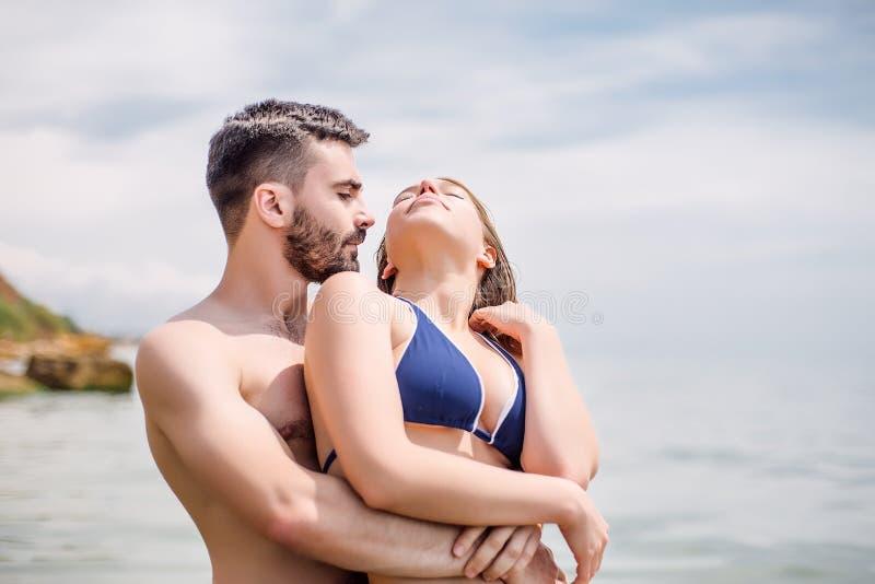 Lyckliga par på havet sätter på land, vuxna människan, sommarferier arkivfoton