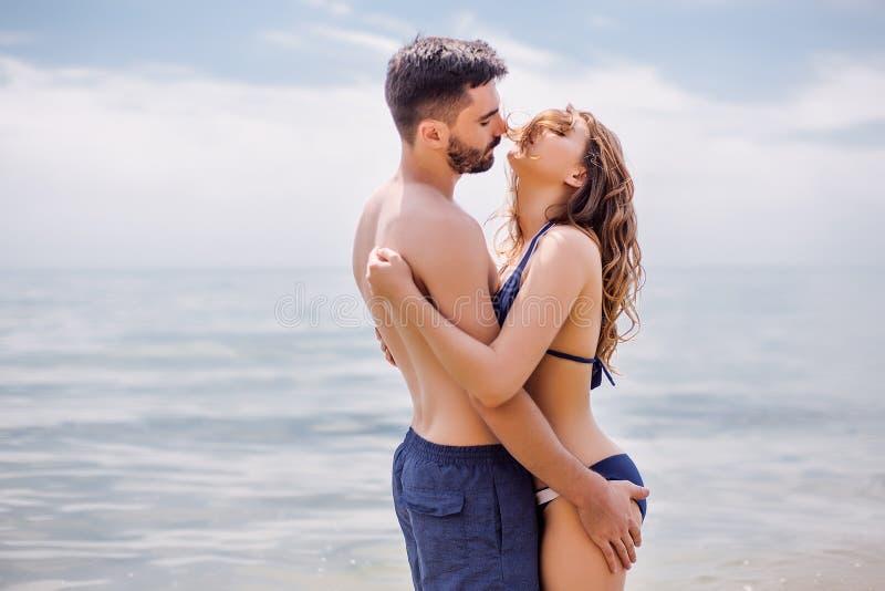 Lyckliga par på havet sätter på land, vuxna människan, sommarferier arkivfoto