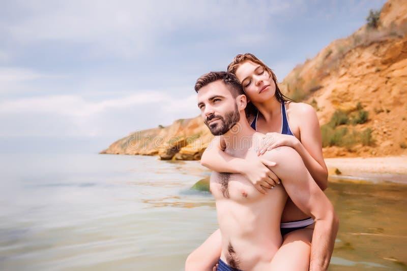 Lyckliga par på havet sätter på land, vuxna människan, sommarferier royaltyfri fotografi