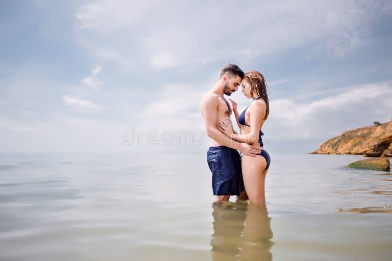 Lyckliga par på havet sätter på land, vuxna människan, sommarferier royaltyfria bilder