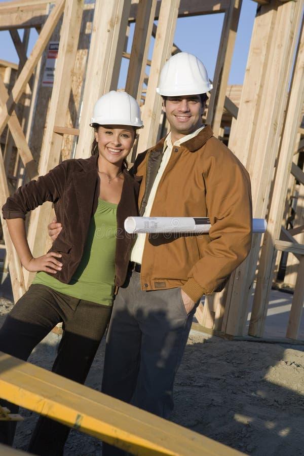 Lyckliga par på konstruktionsplatsen royaltyfri bild