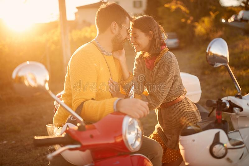 Lyckliga par på sparkcykeln som tycker om i romantisk vägtur på semester på solnedgången royaltyfria bilder