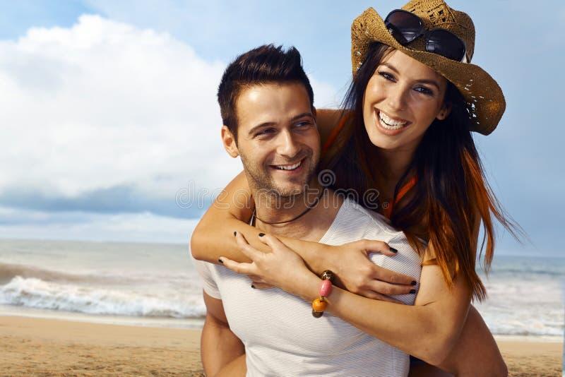 Lyckliga par på stranden arkivbilder
