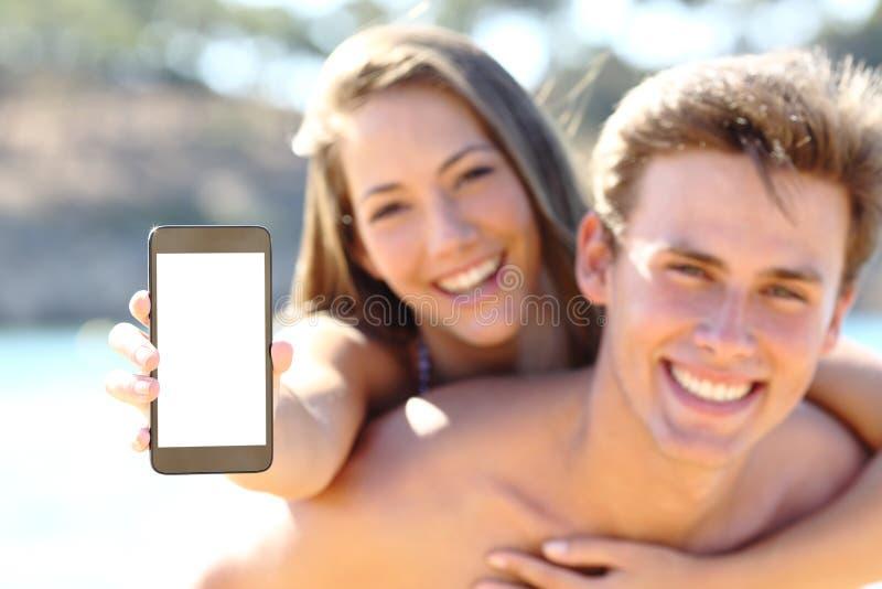Lyckliga par på stranden som visar den tomma telefonskärmen royaltyfria bilder