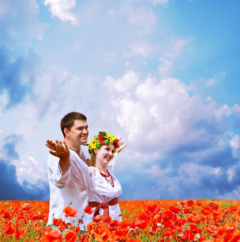 Lyckliga par på vallmofält 3 royaltyfria foton