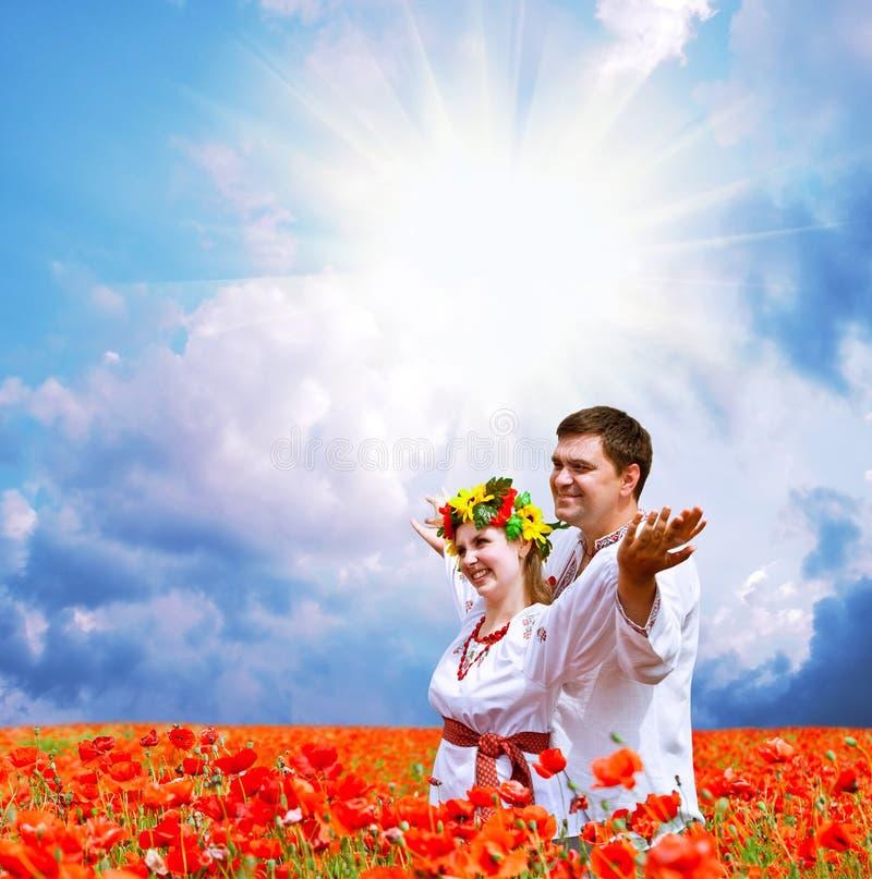 Lyckliga par på vallmofält 2 royaltyfri foto