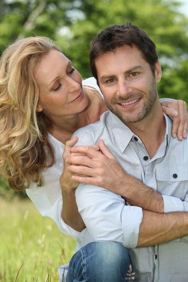 Lyckliga par satt utomhus arkivfoto