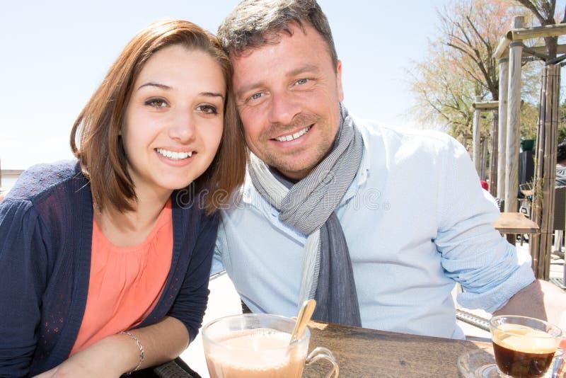 lyckliga par sitter på romans för förälskelse för ferier för kaffeterrasssommar och folkbegrepp royaltyfri fotografi