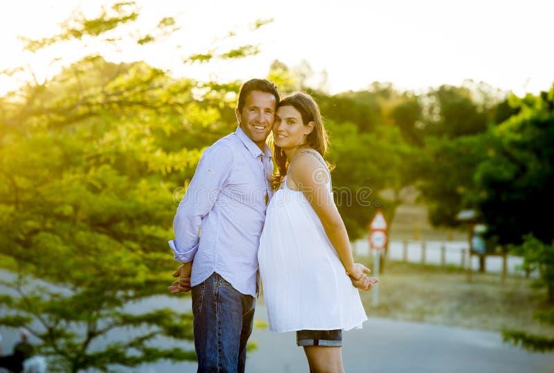 Lyckliga par som är förälskade i, parkerar tillsammans landskap på solnedgång med buken och mannen för kvinna den gravida arkivbild