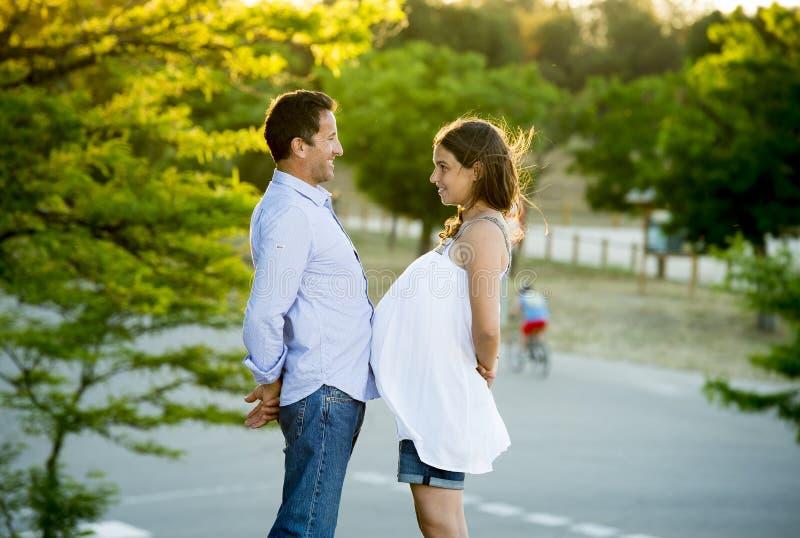 Lyckliga par som är förälskade i, parkerar tillsammans landskap på solnedgång med buken och mannen för kvinna den gravida fotografering för bildbyråer