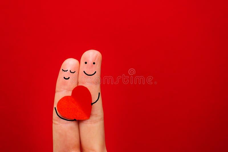 Lyckliga par som är förälskade med den målade smileyen som rymmer röd hjärta - bild royaltyfri foto