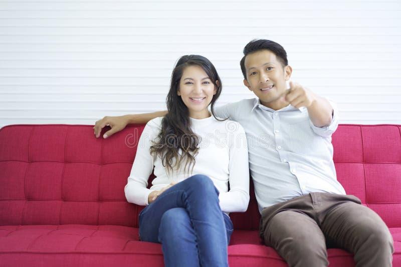 Lyckliga par som är förälskade och tycker om hålla ögonen på massmediainnehållet som hemma kopplar av sammanträde på den röda sof arkivfoto