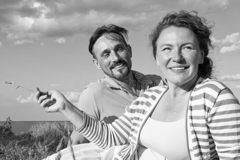 Lyckliga par som är förälskade på en picknick Romantiskt begrepp på stranden Gladlynta par som har gyckel på sommarsemester arkivfoto