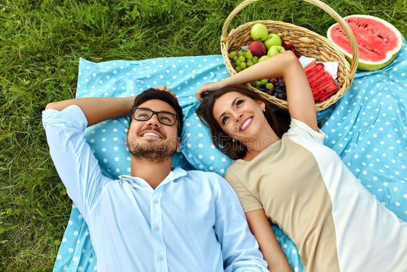 Lyckliga par som är förälskade på romantisk picknick parkerar in förhållande royaltyfri bild
