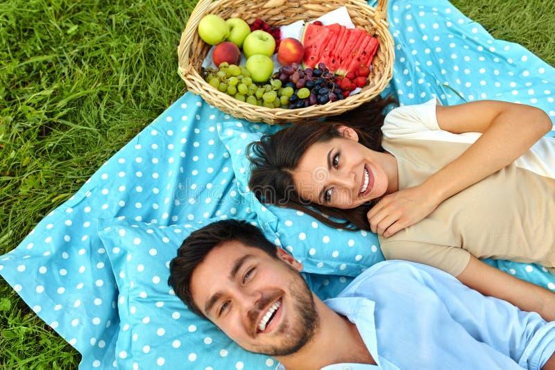 Lyckliga par som är förälskade på romantisk picknick parkerar in förhållande royaltyfri foto