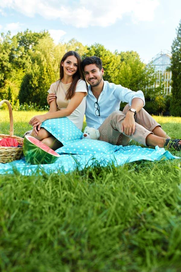 Lyckliga par som är förälskade på romantisk picknick parkerar in förhållande arkivfoto