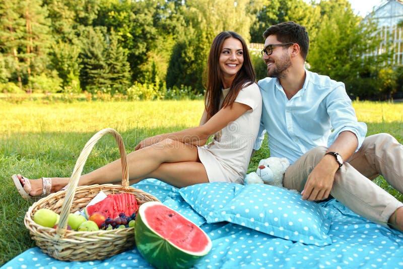 Lyckliga par som är förälskade på romantisk picknick parkerar in förhållande arkivbilder