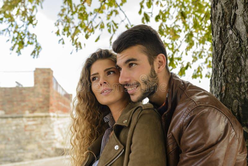 Lyckliga par som är förälskade under trädet arkivbild