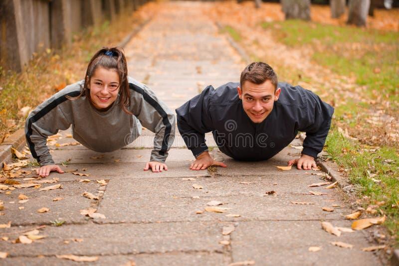Lyckliga par som övar i höst, parkerar De vrider om från jordningen utanför royaltyfri foto