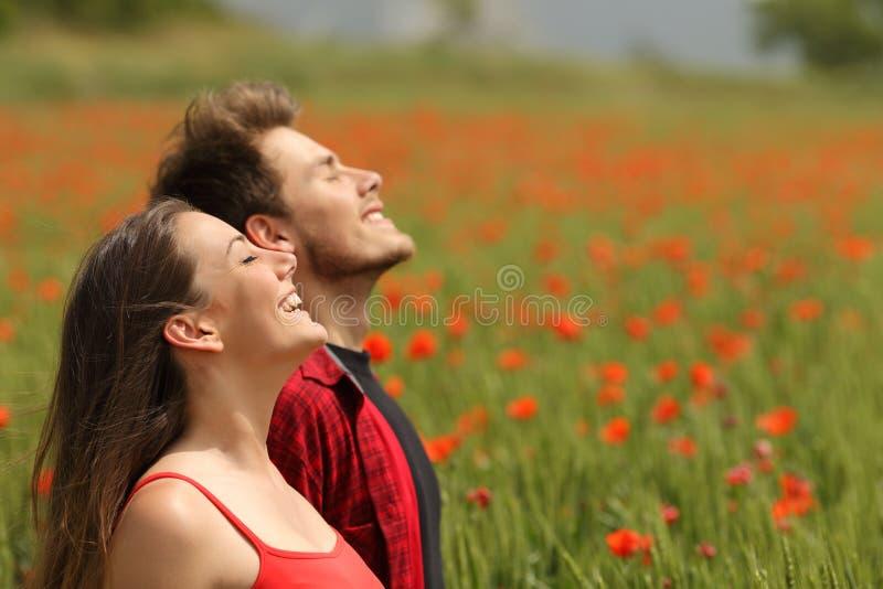 Lyckliga par som andas ny luft i ett rött fält fotografering för bildbyråer