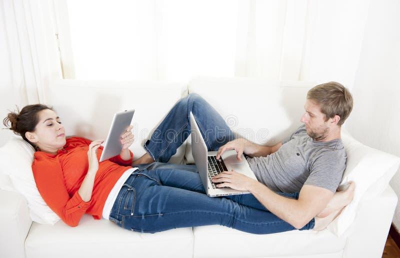 Lyckliga par som arbetar på deras bärbar dator och minnestavlor på en soffa royaltyfri fotografi