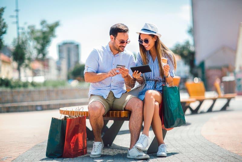 Lyckliga par som betalar på linje med kreditkorten och den digitala minnestavlan fotografering för bildbyråer