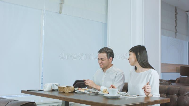 Lyckliga par som betalar räkningen som kommas med av uppassaren och lämnar kafét royaltyfria foton