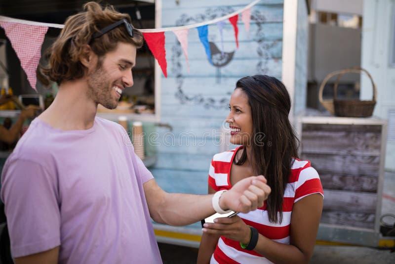 Lyckliga par som betalar räkningen till och med smartwatch royaltyfria bilder