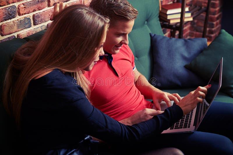 Lyckliga par som bläddrar internet på bärbara datorn, medan sitta på th arkivbild