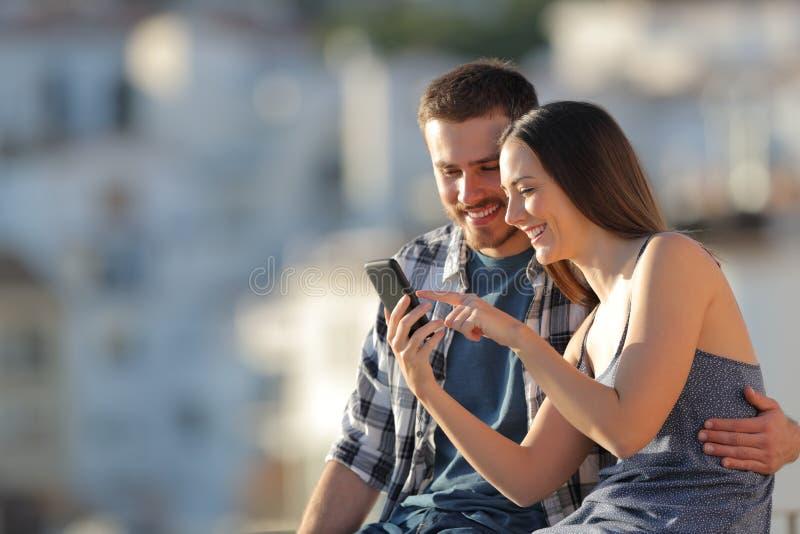 Lyckliga par som bläddrar telefoninnehållet i utkant för en stad royaltyfri bild