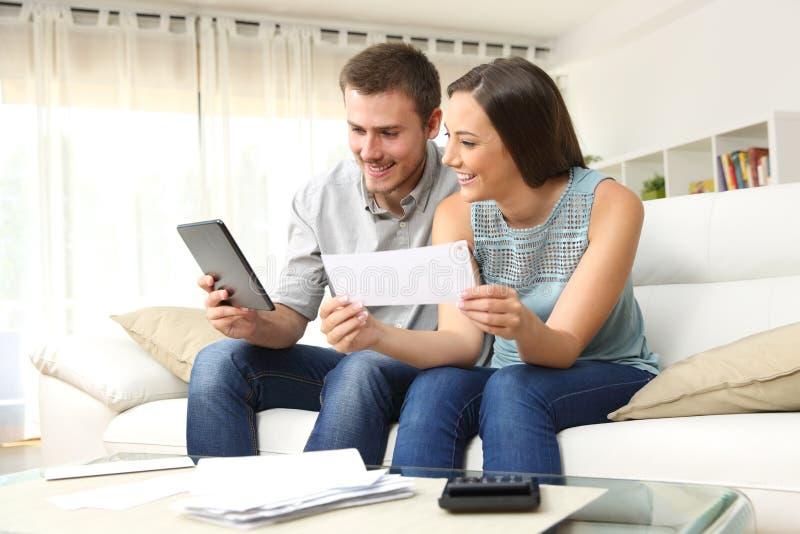 Lyckliga par som direktanslutet kontrollerar bankkonto arkivfoto
