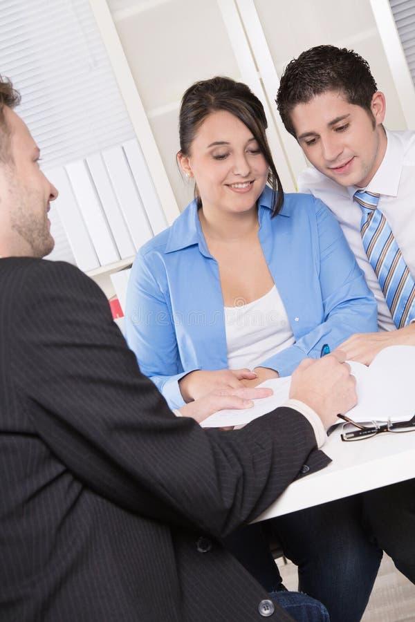 Lyckliga par som diskuterar framtida finansiella plan med konsulent a royaltyfri foto